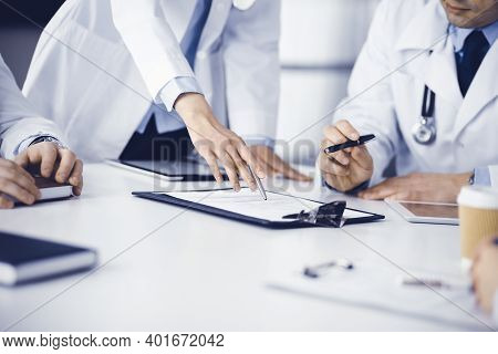Group Of Unknown Doctors Are Sitting At The Desk And Discussing Medical Treatment, Using A Clipboard