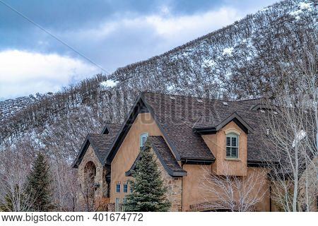 Home With Gable Roofs And Stone Exterior Wall Against Snowy Hill And Cloudy Sky