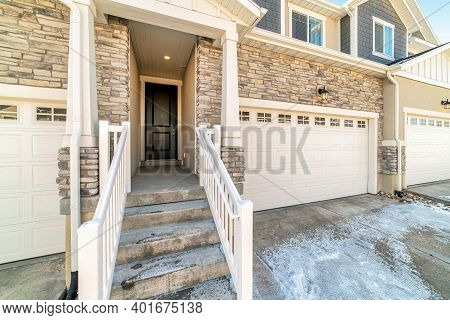 Townhouse Entrance With Concrete Stairs Leading To Front Door Under A Portico