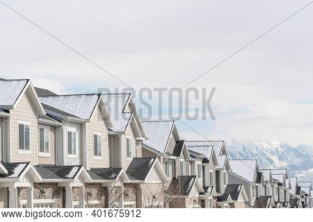 Gabled Townhouses With Scenic Mountain And Overcast Sky Background In Winter