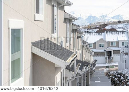 Townhouses With Snowy Gray Roofs And White Wooden Fences Against Overcast Sky