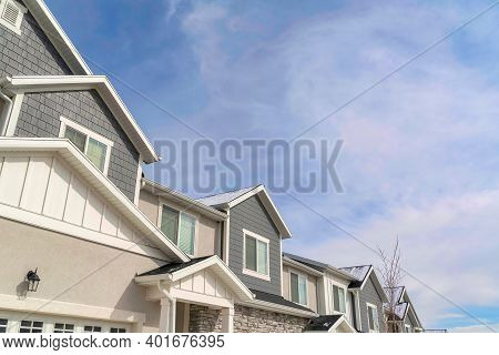 Townhouse Facade With Gray Cladding And Stone Brick Wall Against Cloudy Blue Sky