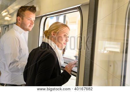 Woman and man looking out train window smiling commuters journey