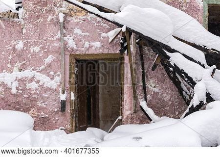 Snow-covered Entrance To An Old Abandoned Building