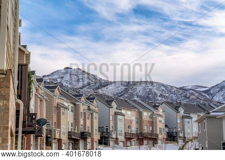 Mountain Peak And Townhouses Against Cloudy Blue Sky Background In Winter