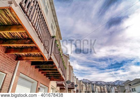 Row Of Townhouses Set Against Cloudy Blue Sky And Snowy Wasatch Mountains