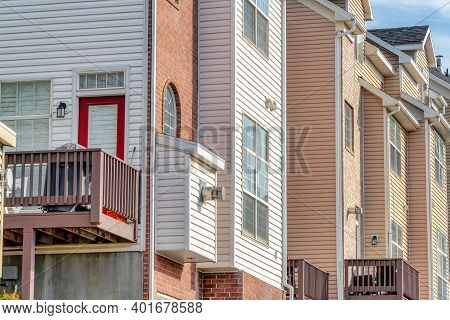 Townhouses Exterior With Balcony Wooden Siding And Brick Wall On A Sunny Day