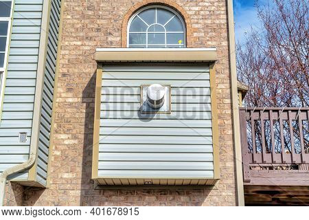 Close Up Of Townhouse Exterior With Brick Wall And Arched Window On A Sunny Day