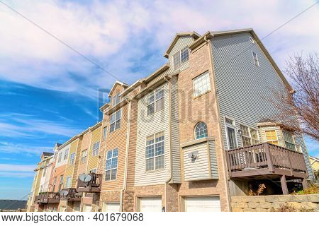Townhouses With Dormers Balconies Attached Garages Sidings And Stone Brick Walls