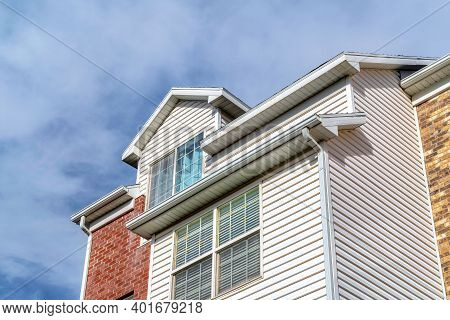 Dormer And Upper Floor Exterior Of A Townhouse Against Clouds And Blue Sky