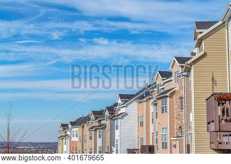 Townhouses On A Sunny Neighborhood With Views Of The Valley And Cloudy Blue Sky