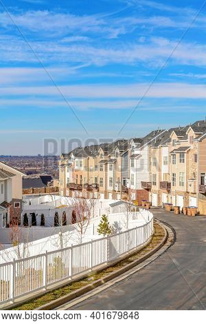 Road Along Townhouses That Looks Out To The Valley Against Blue Sky And Clouds