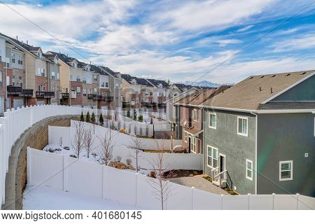 Snowy Neighborhood Landscape Of Home With Backyards And Townhouses Along Road