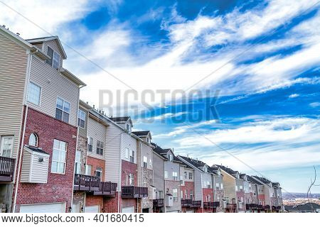 Three Storey Townhouses In A Row With Valley And Cloudy Vibrant Blue Sky Views