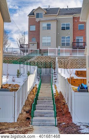 Stairways Amid Townhouses And Homes At A Sunny Neighborhood With Snowy Terrain