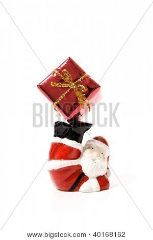 Santa Claus playig with a gift on a white background.