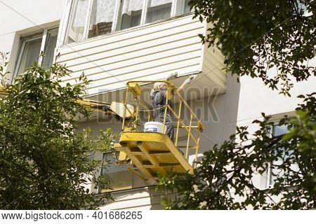 Woman Builder On A Construction Cradle Repairs A Balcony Outside. Overhaul Of A Residential Building