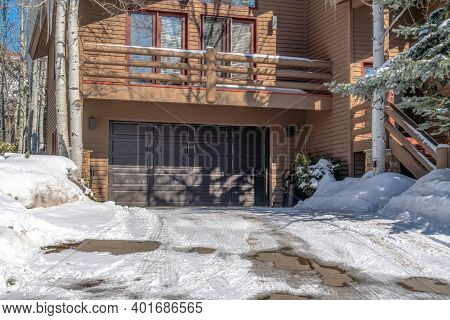 Snowy Driveway That Leads To The Garage Of Home With Balcony And Brown Wall