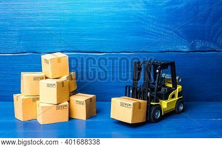 Forklift Truck And Cardboard Boxes With Goods. Logistic Infrastructure And Warehousing Services. Tra