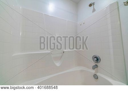 Stainless Steel Shower Fixture And Polished Built In Bathtub Inside Bathroom