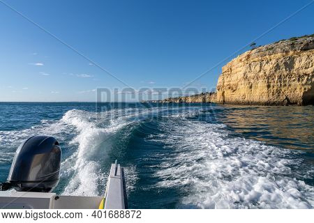 An Outboard Motor Of A Speeding Coast With Ocean And Rocky Coast Behind