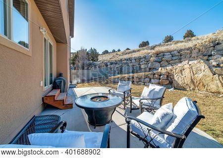 Fire Pit And Paved Patio At Sunny Backyard Of House With Stone Retaining Wall