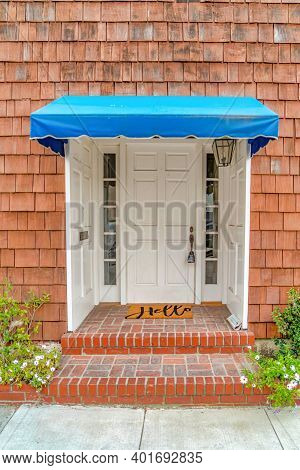 Blue Overhang Over Entrance Of Home With Shingle Wall Cladding In Long Beach Ca