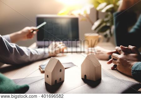 Buying A New House Concept. Real Estate Agent Explaining A Plan Design On Computer Laptop With Coupl