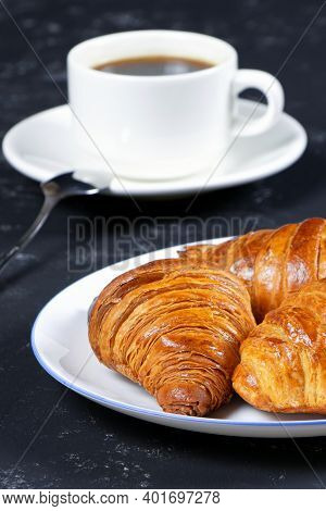 A Cup Of Hot Coffee And Croissants On A Black Background. Breakfast With Coffee And Fresh Pastry. Co