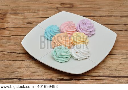 A Plate With Pastel Colored Meringues On A Wooden Table