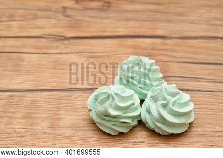 Three Green Meringues On A Wooden Background