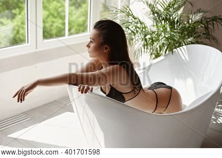 Young Sexy Woman With Great Body Shape In Beige Lingerie Posing In A Bathtub. Model Girl Perfect Bod