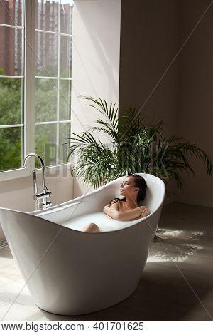 Beautiful Sexy Brunette Model Takes A Bath With Milk And Sea Salt. Young Woman Enjoying Spa Treatmen