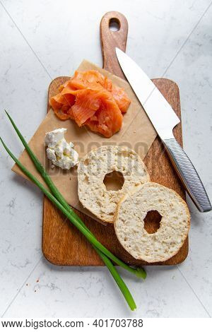 Breakfast Composition With Bagels And Smoked Salmon On A Cutting Board, On A Marble Background, Top