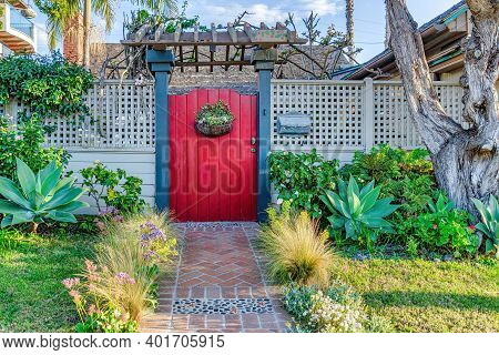 Landscaped Garden With Pathway Inside White Fence And Red Gate With Pergola