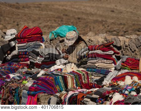 Indigenous Woman Selling Traditional Colorful Handwoven Wool Textile Clothing At Main Road From Colc