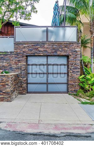House Garage With Glass Paned Door Under Balcony With Glass Railing In San Diego