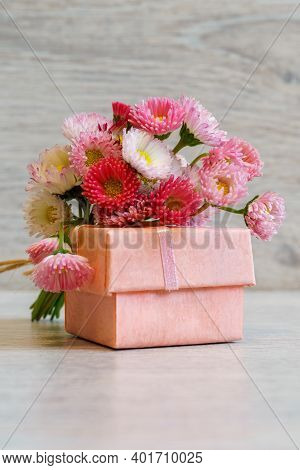 Bouquet Of Fresh Pink Marguerite Daisy Flowers And Small Gift Box Lying On Light Background. Spring