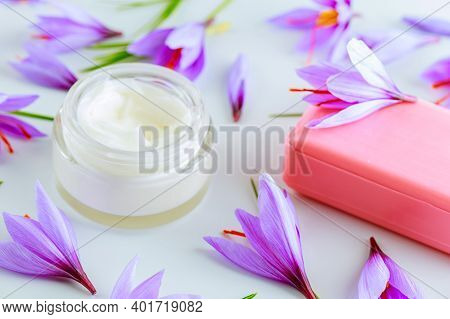 Saffron In A White Plate And Cosmetic Cream On A White Background. Cream With Saffron Extracts.