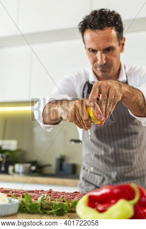 A Chef Squeezing Lemon Juice On Carpaccio Meat On A Wooden Kitchen Board.