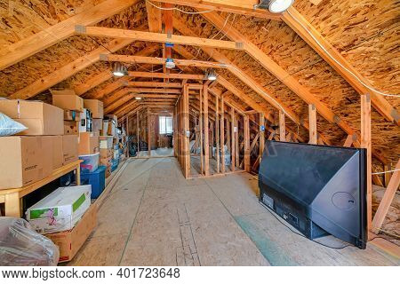 Interior Of The Attic Of House With Boxes And Old Appliances Under Gable Roof