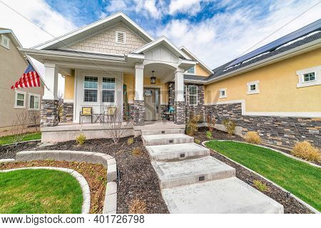Single Storey Home With Gable Roofs And Arched Entrance To The Open Porch