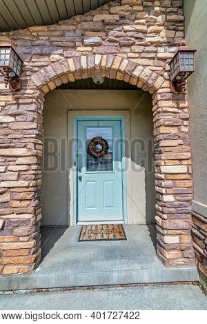 Stone Brick Arch And Glass Paned White Front Door At The Entrance Of A House