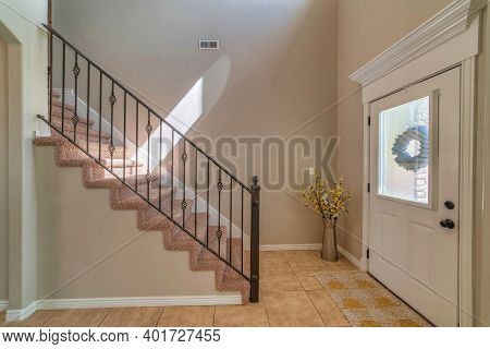 House Interior With Glass Paned White Front Door And Stairs At The Entryway