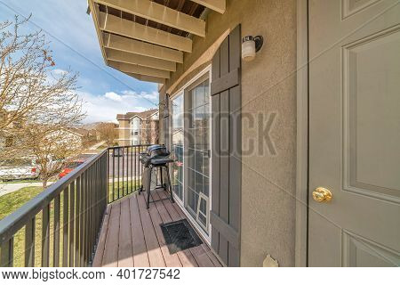 Barbecue Grill On Small Balcony With Roof Overhang And Huge Window With Shutters