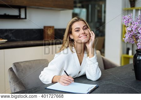 A Lovely Young Woman Is Sitting At The Table In Her Kitchen And Writing In A Notebook. Making A Home