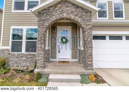 Beautiful Facade Of Home With Arched Stone Entrance And Glass Paned Front Door