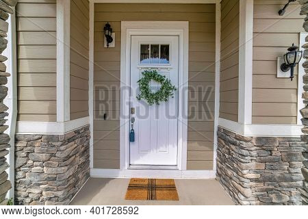 White Wooden Front Door With Glass Panes And Wreath At The Facade Of House