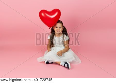 Lovable, Charming, Girl In A White Dress Holding A Red Heart Shaped Balloon And Sitting Cross-legged
