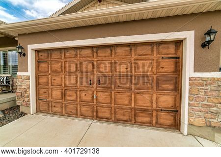 Wide Brown Wooden Panelled Garage Door Of An Attached Garage With Wall Lamps